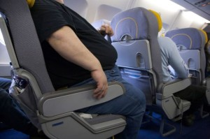 Very big obese person traveling by airplane. BAGJA7.